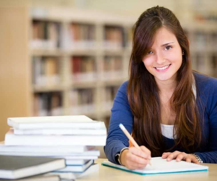 Happy female student at the library smiling